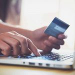Woman typing on a computer while holding her credit card